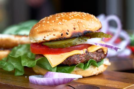 Deliciosa hamburguesa con queso apilada con una jugosa empanada de ternera, queso, lechuga fresca, cebolla y tomate en un bollo fresco con semillas de sésamo de pie sobre papel marrón sobre una mesa de madera con copyspace Foto de archivo