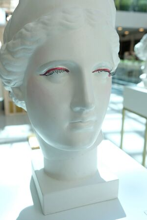 White bust of young woman in the Mall. bust of an ancient woman with false eyelashes and arrows Banque d'images - 129110330
