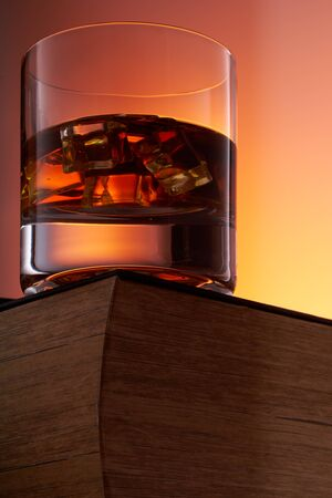 glass of whiskey with ice on an old book. bottom view. close up Stockfoto