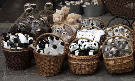 wicker baskets with soft toys on the sidewalk. sale of soft toys: penguins, pandas, sloths, camels, meerkats, monkeys.