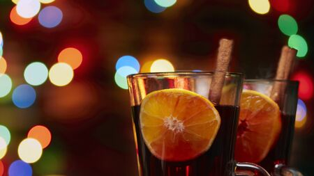 Christmas mulled wine red in a glass with a stick of cinnamon and a piece of orange on a background of twinkling lights