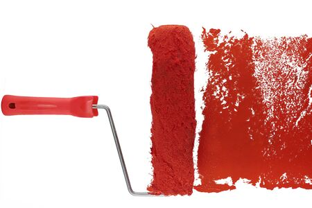 red paint roller leaving a smear of red paint on a white sheet. white background