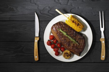 Barbecued Steak on a plate Served with corn and Tomatoes. Dark background, top view, horizontal photo