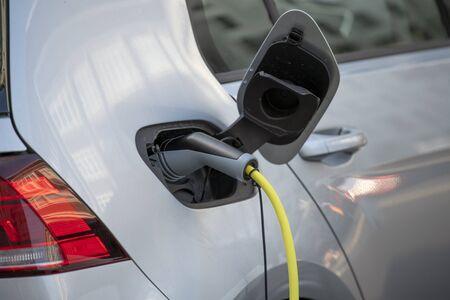 Coche eléctrico color plateado: enchufado para cargar. estación de carga para coche eléctrico. Cerca de la fuente de alimentación conectada a un coche eléctrico que se está cargando. Cable de carga para coche.