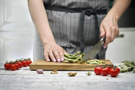 The chef prepares green beans, tomatoes on a branch, red onions in the white kitchen. wooden cutting Board on rustic background Archivio Fotografico