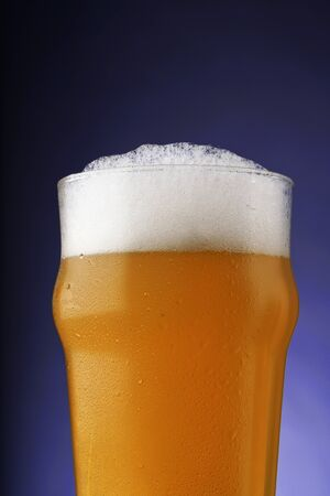 A pint of beer with foam in a glass with water drops on a dark background with gradient lighting