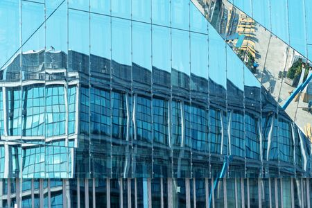 old building is reflected in the glass surface of the modern building