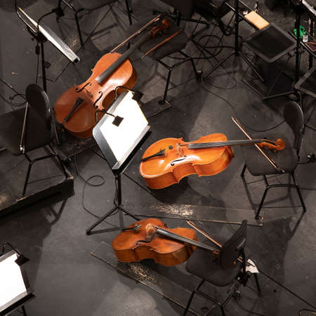 three cellos in the orchestra pit among the chairs and sheet music