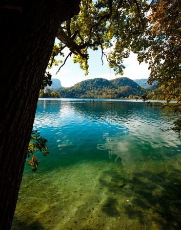 blue water at lake bled with mountains in the background