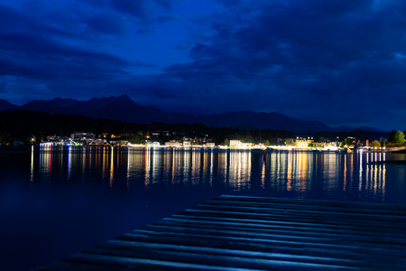 colored clouds over lake with a pier in the middle and reflection in the water. Captured on Woerthersee, Kaernten, Austria. Stock Photo