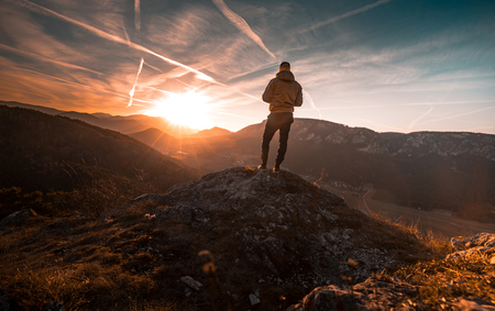 Man stands on the peak of a mountain and watching to Sun. Beautiful moment the miracle of nature during Sunset in Austria