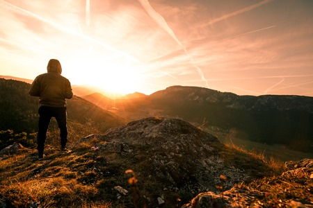 Man stands on the peak of a mountain and watching to Sun. Beautiful moment the miracle of nature during Sunset in Austria 写真素材 - 120446212