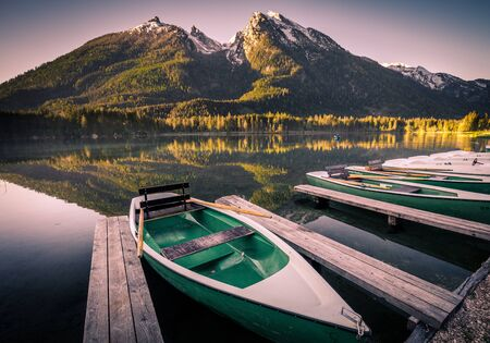 Morning scenery with boats moored on Hintersee lake at sunrise, Bavaria, Germany in summer