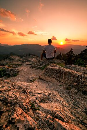 Man on top of mountain. Conceptual scene on Hohe Wand in Austria during Sunset Stock fotó