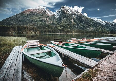 Beautiful evening view on Hintersee Lake with moored boats on foreground and sunlit mountain hills on background. Location: resort Ramsau, National park Berchtesgadener Land, Upper Bavaria, Germany. 版權商用圖片