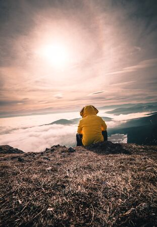 Hiker man take a rest on mountain peak. Man sit on sharp summit and enjoy spectacular view. Colorful autumn landscape. Bright morning Sun shining in sky in austria hohe wand