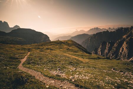 Mountains in morning sunrise light with sun flare in the dolomites italy during summer