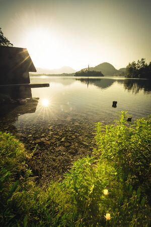 First light of sunrise on silhouette tower of Assumption of Mary church at Lake Bled in summer