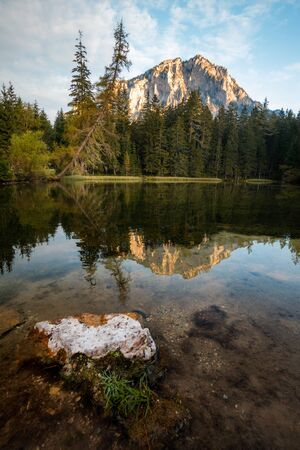 Mountain reflection in a lake in austria during autumn at sunrise