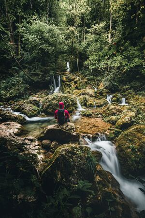 Hiker standing in front of a waterfall surrounded by rocks in the forest in austria in autumn Stockfoto - 131595742