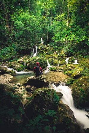 Hiker standing in front of a waterfall surrounded by rocks in the forest in austria in autumn