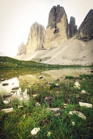 Three Peaks in the Dolomites reflecting in a lake, Italy during summer