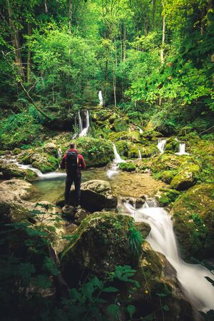 man with backpack sits on stone at a waterfall in the forest and meditates alone in austria