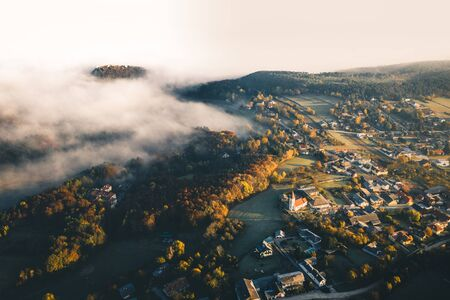 Small town village during the sunrise with fog. surrounded by hills in lower austria. Aerial drone photo Stockfoto