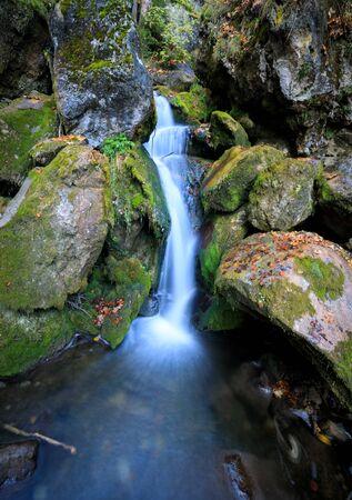 Wooden bridge over cascade falls over mossy rocks at Myrafalle, near Muggendorf in Lower Austria