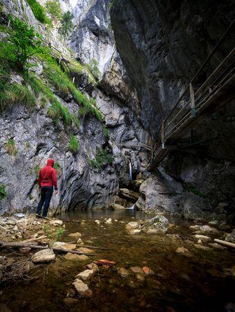 man is standing at a canyon in the baerenschuetzklamm in austria during summer