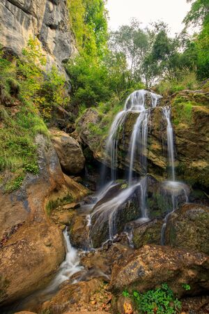 Waterfall in Autumn forest. Beautiful nature background.
