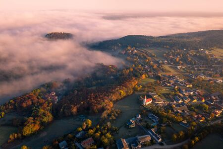 Small town village during the sunrise with fog. surrounded by hills in lower austria. Aerial drone photo