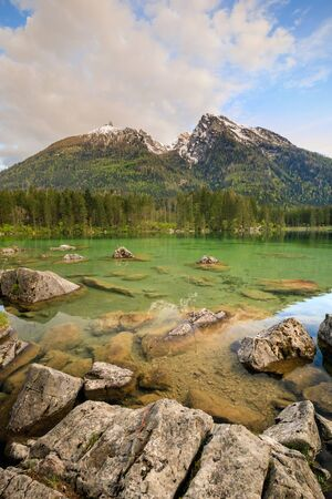 The still snow-covered mountains at lake hintersee in germany in summer