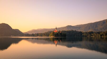 First light of sunrise on silhouette tower of Assumption of Mary church at Lake Bled. Julian Alps still in shadow in background. Blue sky in Summer