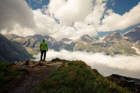 Wide mountain panorama. Small silhouette of Person on rocky mountain slope covered with white puffy clouds and Fog.