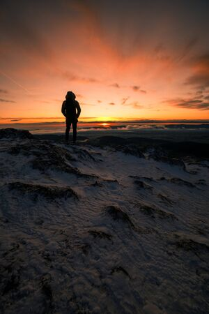 Hiker is standing on a Mountain Peak watching the Sunrise in Winter in the austrian Alps