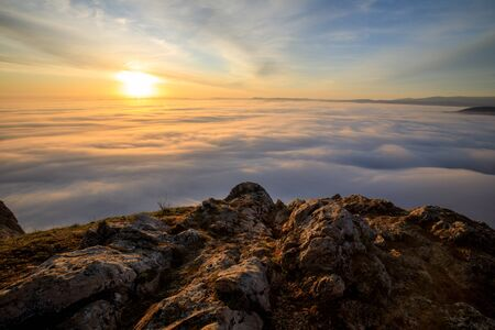 sunrise on a mountain peak with a lot of fog and clouds in austria Stock fotó