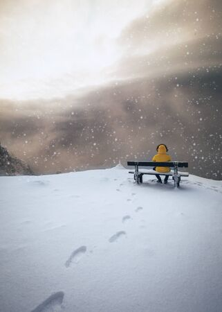 Man sitting on a wooden bench on Mountain Peak in Winter with a lot of Snow in Austria