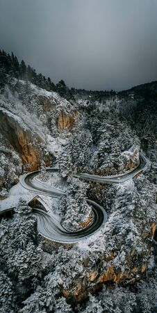 Curvy windy road in snow covered forest, top down aerial view. Winter landscape in austria