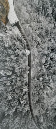 Aerial view of snowy forest with a road. Captured from above with a drone in Austria 版權商用圖片