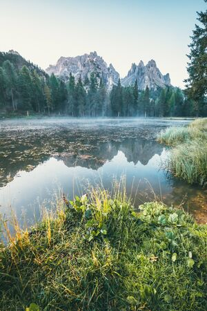 Italian Dolomites reflecting on the lake of Antorno on a summer day in the morning with fog on the water