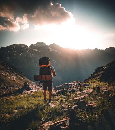 Man traveler hiking alone in breathtaking landscape of austrian Mounatins at sunset. Travel Lifestyle wanderlust adventure concept. Outdoor wilderness vacations. 版權商用圖片