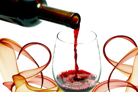 Red wine pouring down from a wine bottle, isolated on white photo