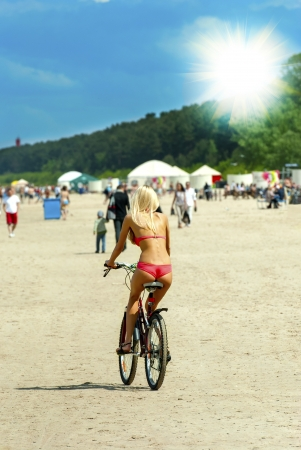 Young woman riding bike on the summer beach photo