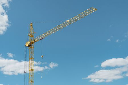 Industrial theme. Yellow construction crane against blue sky. High quality photo