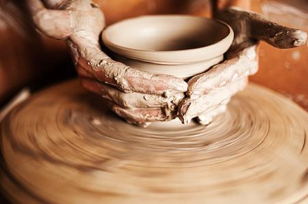 Manos de una mujer la creación de una vasija de barro en el torno de alfarero Foto de archivo - 92609535