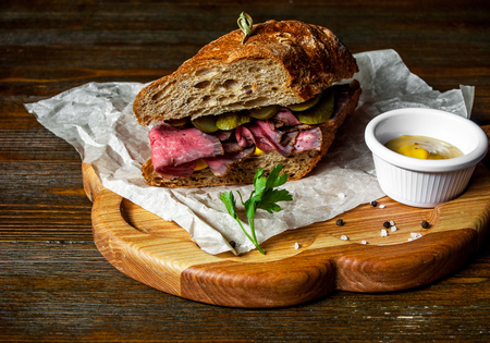 Pastrami sandwich on rye bread with pickles and mustard sauce, served on a wooden plate