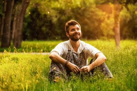 Heureux homme gai assis sur une herbe dans le parc, souriant et perdu dans ses pensées
