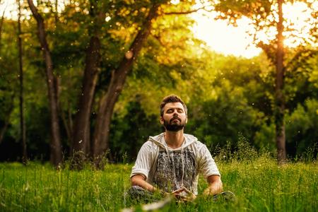 Um homem farpado está meditando sobre a grama verde no parque com a cara levantada até o céu e os olhos fechados no dia de verão ensolarado. Conceito de meditação, sonho, bem-estar e estilo de vida saudável