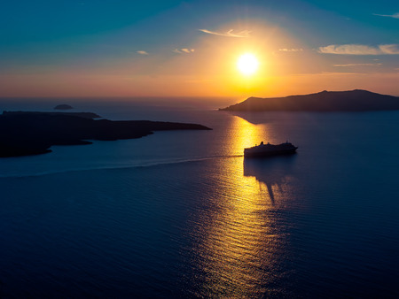 Cruise ship silhouette in sunset light with a few islands on background Stock Photo